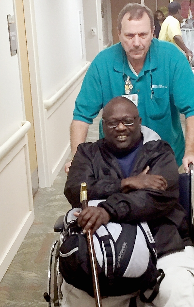 Charles Groover pushes Larry Hall in a wheelchair.