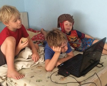 Three boys on a bed looking at baby brother on computer screen.